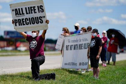 El reverendo Sylvester Edwards se arrodilla mientras otros manifestantes sostienen carteles cerca del Complejo Correccional Federal de Terre Haute, Indiana, para mostrar su oposición a la pena de muerte y la ejecución de Daniel Lewis Lee (REUTERS / Bryan Woolston)