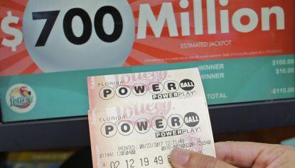 Un cliente sostiene un ticket que pariticpó del sorteo, sin éxito (AP)