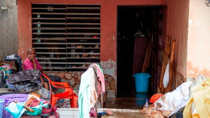 A man sits outside his house next to his waxes damaged and wet by the heavy rains (EFE / Henry Chirinos)
