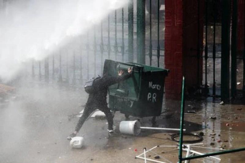 Un manifestante empuja un tacho de basura durante los disturbios que dejaron 17 detenidos a 47 años del Golpe Militar. REUTERS/Ivan Alvarado