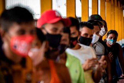 Personas hacen fila hoy para votar en el único centro electoral de la comunidad Lago do Catalao, en zona rural de Iranduba, Amazonas (Brasil). EFE / RAPHAEL ALVES