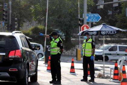 La policía israelí revisa un automóvil en un punto de control después de que Israel ingresó a un segundo bloqueo en todo el país en medio de un resurgimiento de nuevos casos de enfermedad por coronavirus (COVID-19), lo que obligó a los residentes a permanecer principalmente en casa durante la temporada alta de vacaciones judías, en la entrada a Jerusalén. REUTERS/Ronen Zvulun