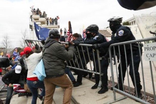 Partidarios del presidente Trump se enfrentan a los oficiales de policía fuera del edificio del Capitolio en Washington este 6 de enero de 2021. REUTERS/Leah Millis