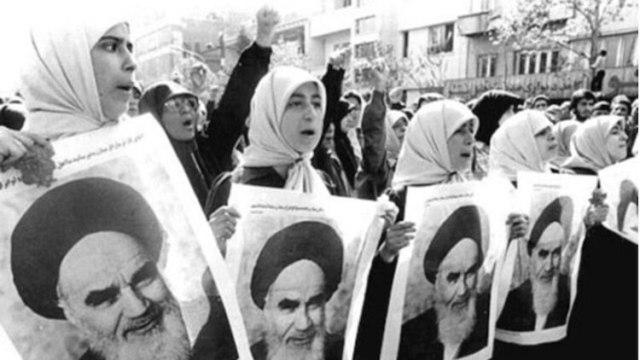Mujeres vestidas con velo llevando carteles del AyatoláRuhollah Kkomeini
