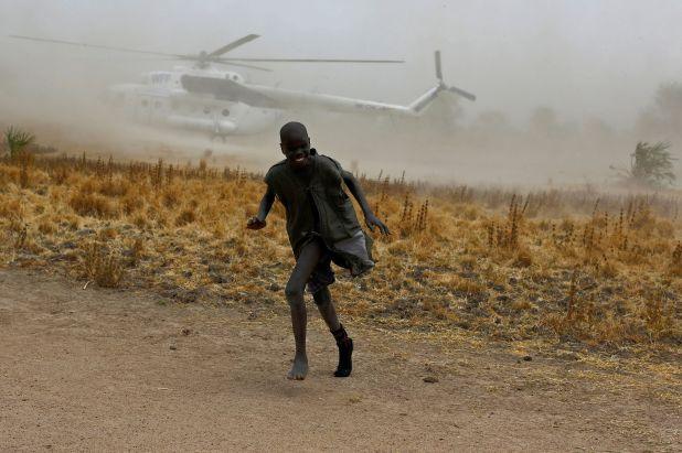 Un niño se aleja cuando un helicóptero del Programa Mundial de Alimentos (PMA) de las Naciones Unidas aterriza en la aldea de Rubkuai, en el estado de Unity, al norte del Sudán del Sur, el 18 de febrero de 2017 (REUTERS/Siegfried Modola)