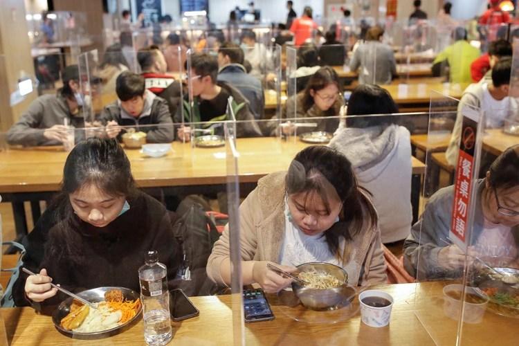 Estudiantes almuerzan entre divisores para protegerlos del coronavirus en la cantina de la Universidad Nacional de Ciencia y Tecnología de Taiwán (NTUST) en Taipei (Reuters)