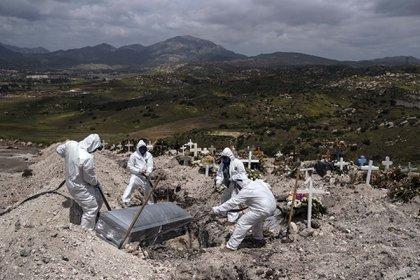 Trabajadores con trajes especiales sepultan el cuerpo de una víctima de covid-19 que nadie reclamó en el cementerio municipal de Tijuana, México (21 de abril)