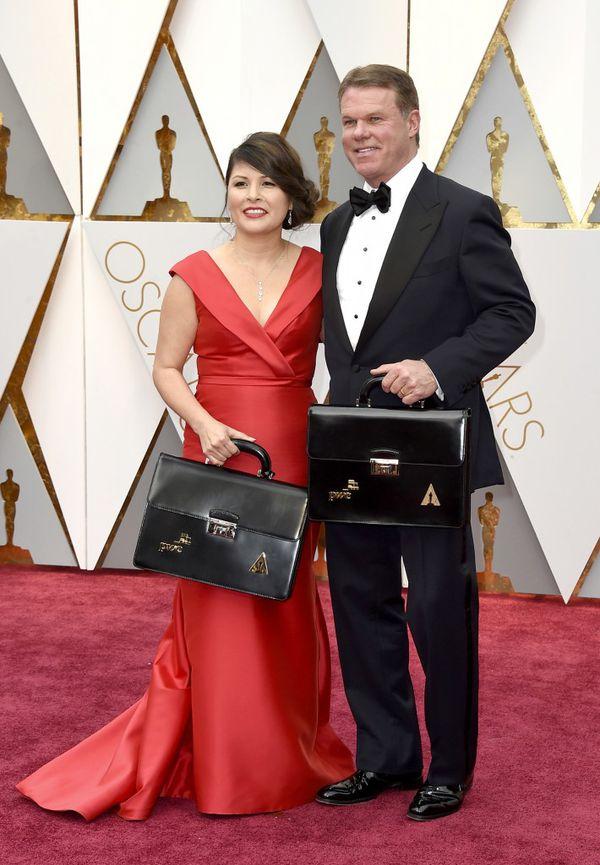 Martha Ruiz y Brian Cullinan en el momento de ingresar al Teatro Dolby con los maletines donde se custodian los resultados de las 24 categorías de los Premios Oscar. (AP)