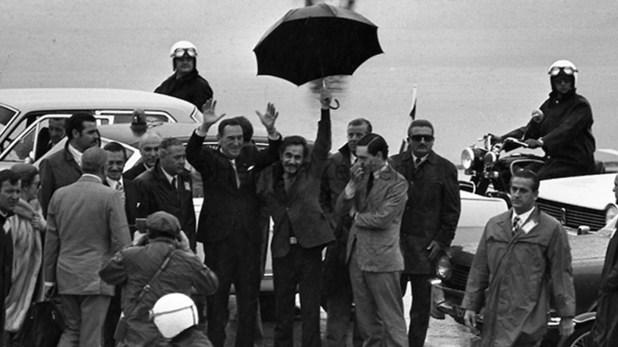 José Ignacio Rucci sostiene el paraguas que protege de la lluvia a Juan Domingo Perón el día de su regreso a la Argentina tras 18 años de exilio
