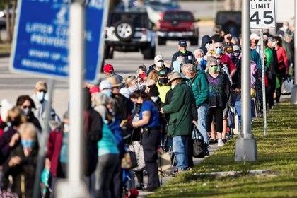 Cientos de personas esperan en fila en el Lakes Park Regional Library para recibir la vacuna COVID-19 en Fort Myers, Florida, EE.UU. 30 de diciembre de 2020. Fotografía tomada el 30 de diciembre de 2020. Andrew West / The News-Press / USA TODAY NETWORK vía REUTERS.