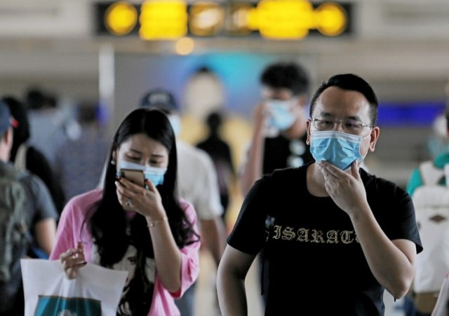 Pasajeros con máscaras al pasar frente a una máquina de escaneo que controla la temperatura de las personas tras el nuevo brote de coronavirus en China, en el aeropuerto internacional de Bandaranaike en Katunayake, Sri Lanka, el 24 de enero de 2020 (REUTERS/Dinuka Liyanawatte)