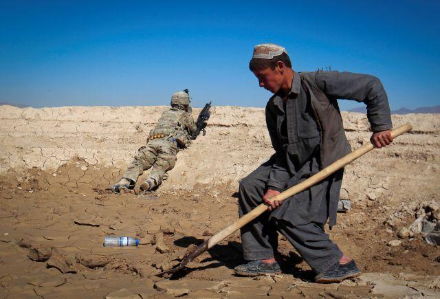 Un niño afgano trabaja en una obra de construcción mientras un soldado del Ejército de Estados Unidos de la Fuerza de Tarea 3/1 AD Bulldog toma posición durante una patrulla conjunta con el Ejército Nacional Afgano (ANA) en una aldea del distrito de Kherwar en la provincia de Logar, al este de Afganistán, el 23 de mayo de 2012.