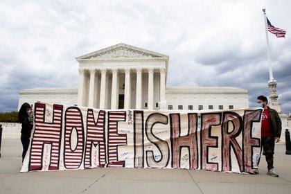"""Dos personas sostienen un cartel que dice """"Aquí es nuestro hogar"""" fuera del Tribunal Supremo de Estados Unidos (EFE/EPA/MICHAEL REYNOLDS)"""
