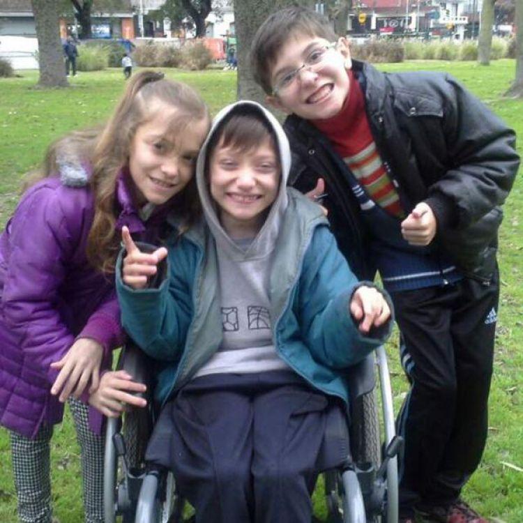 Los trillizos Rafael, Gustavo y Nicole, quienes, junto a su madre Ángela, ayudan de manera constante en el tratamiento y asistencia para su hermano