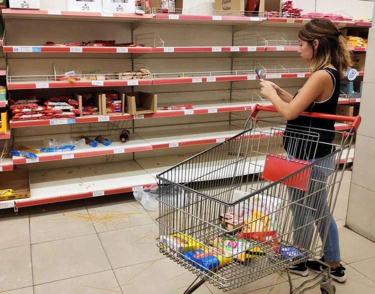 Una mujer toma una foto de fideos desparramados en el piso frente a estantes de pasta vacíos en un supermercado, mientras la gente acudía a comprar comida por el brote de coronavirus, en Buenos Aires, Argentina, el 15 de marzo de 2020 (REUTERS/Agustin Marcarian)