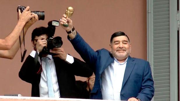 Maradona, con una mini réplica de la Copa del Mundo, 33 años después