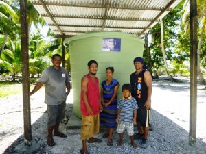 A Lae family poses with their new water catchment. Carpenter Jeffrey Andaya is at left. Photo: Dustin Langidrdik