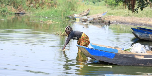 A woman collects water for domestic use at oneof the fishiong grounds along Lake Nakivale