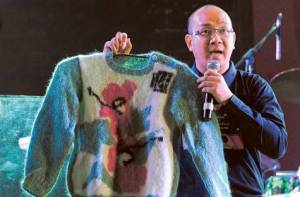 A presenter displaying one of the sweaters