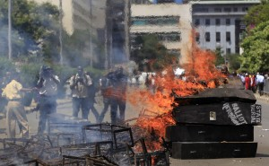 Mock coffins burn outside the Kenyan parliament during a protest against legislators planning to receive higher bonuses, in Nairobi