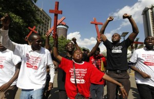 Protesters chant slogans as they carry wooden crosses during the #OccupyHarambeeAve protest in Nairobi