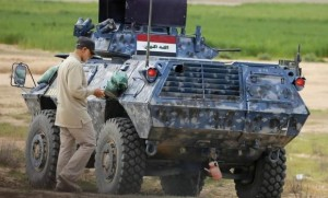 Iranian Revolutionary Guard Commander Soleimani walks near an armoured vehicle at the frontline during offensive operations against Islamic State militants in the town of Tal Ksaiba