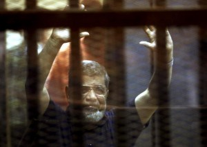 Former Egyptian President Mohamed Mursi reacts behind bars with other Muslim Brotherhood members at a court in the outskirts of Cairo, Egypt May 16, 2015.REUTERS/Mohamed Abd El Ghany