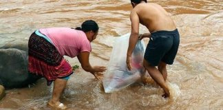 So Sad: This Parent Have To Carry Their Kids In Plastic Bag To cross A River Every Day Just So They Can Go To School Dry