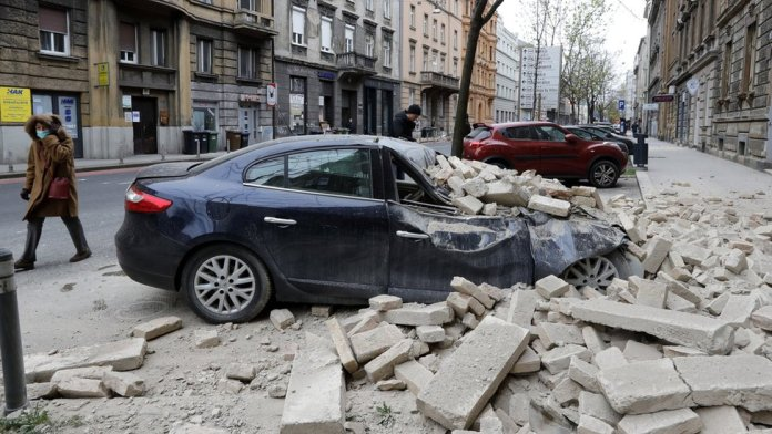 A person walks past rubbles lying on a street after a 5.3-magnitude earthquake that hit near Zagreb, Croatia, 22 March 2020