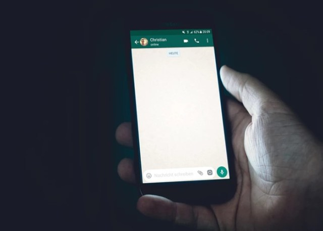 Pessoa segurando um celular com o Whatsapp aberto na tela
