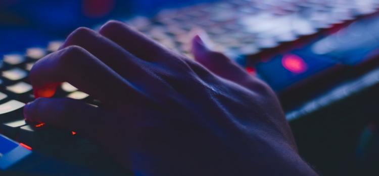 Color photo of a human hand typing on a keyboard