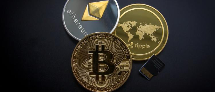 Color photo of three coins with inscriptions: etherum, ripple and bitcoin logo.
