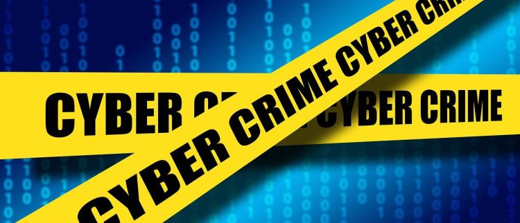 Color photo of cyber crime inscription on a yellow tape, on a blue background.