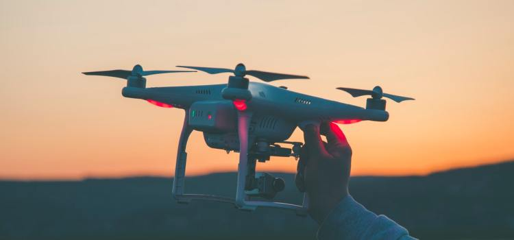 Color photo of a mans' hand holding a drone in the air, used to illustrate the meaning of drones and privacy concerns.