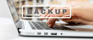 Color photo of human hands typing on laptop keyboard, with the inscription ''backup'' in front.