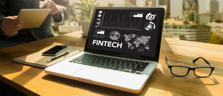 Color photo of fintech laptop with visual data on a screen.