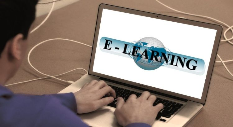 Color photo of a man typing on a laptop with e-learning on screen used to illustrate the importance of taking cybersecurity courses online.