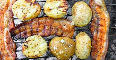 Wer bei Grillkartoffeln auf Alufolie verzichten will, muss die Knollen vorkochen. Sie werden dann halbiert auf den Rost gelegt. Foto: Markus Scholz/dpa-tmn