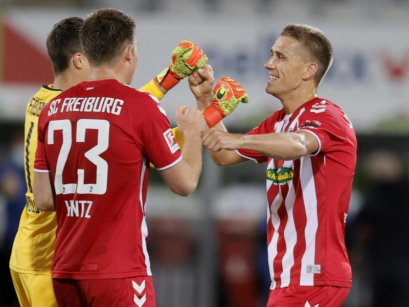 Freiburgs Nils Petersen (r) feiert den Sieg mit Dominique Heintz (M) und Torwart Alexander Schwolow. Foto: Ronald Wittek/epa/Pool/dpa