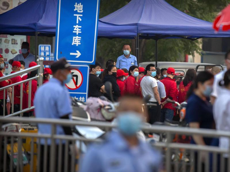 Polizisten sichern einen Fleischmarkt, der von den Behörden geschlossen wurde, nachdem bekannt wurde, dass ein Besucher des Marktes positiv auf das Coronavirus getestet worden war. Foto: Mark Schiefelbein/AP/dpa
