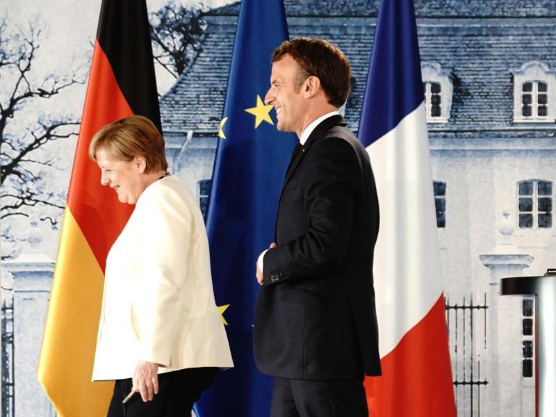 Angela Merkel und Emmanuel Macron verlassen die Pressekonferenz nach ihrem Treffen im Schloss Meseberg. Foto: Kay Nietfeld/dpa-Pool/dpa
