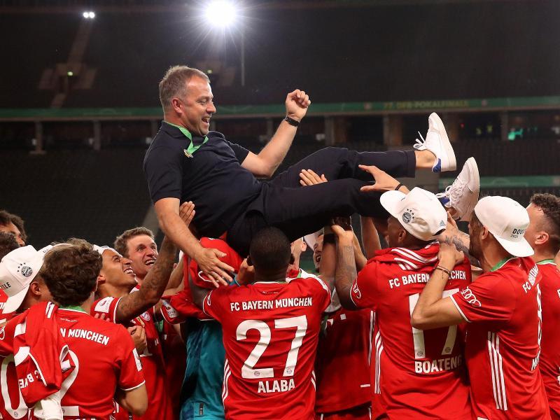 Münchens Trainer Hansi Flick wird von seinen Spielern in die Luft geworfen. Foto: Alexander Hassenstein/Getty Images Europe/Pool/dpa