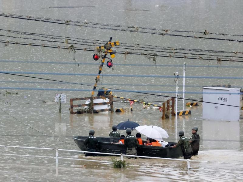 Mit einem Boot werden Bewohner in Kuma in Sicherheit gebracht. Foto: Kota Endo/Kyodo News/AP/dpa