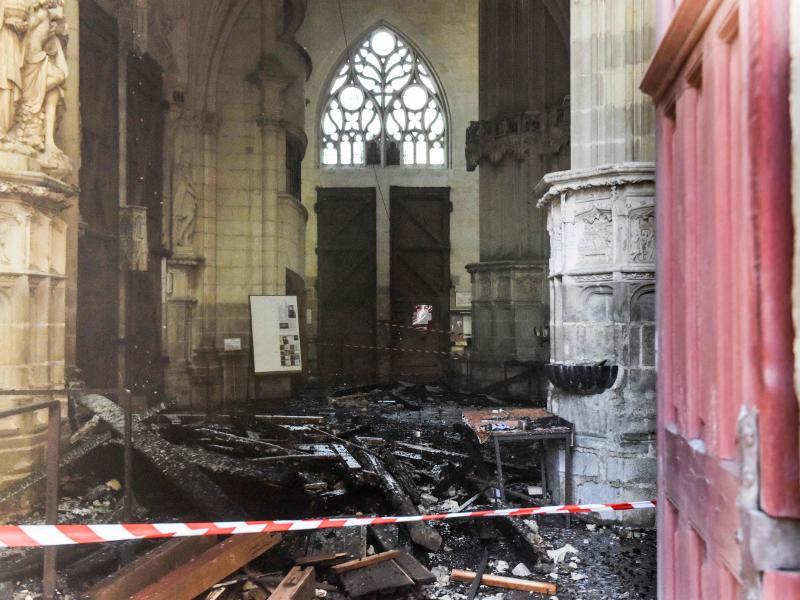 Verkohlte Trümmer liegen in der Kathedrale Saint-Pierre-et-Saint-Paul nach einem Brand. Foto: Sebastien Salom-Gomis/AFP/dpa