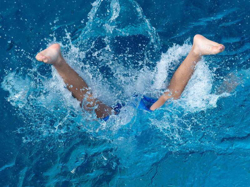 Ein Junge springt im Münchner Michaelibad vom Sprungturm ins Wasser. Foto: Sven Hoppe/dpa