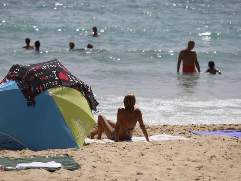 Eine Frau sonnt sich am Strand von Cala Major. Foto: Clara Margais/dpa