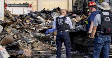 Polizisten begutachten den Schaden an einem Geschäft für Bürobedarf, das bei einem Protest ausgebrannt ist. In Kenosha kam es die zweite Nacht in Folge zu Ausschreitungen. Foto: Morry Gash/AP/dpa