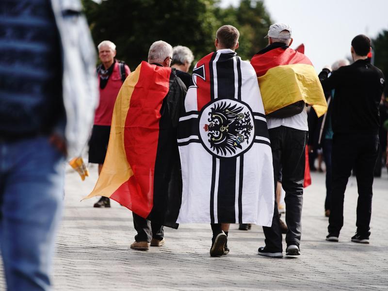 Ein Demonstrant trägt die Reichskriegsflagge. Foto: Kay Nietfeld/dpa