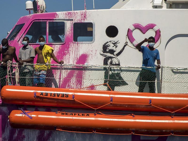 Ein Junge an Bord der «Louise Michel», das vom renommierten Künstler Banksy finanziert wird, winkt der Besatzung des Rettungsschiffes «Astral». Das Rettungsschiff «Louise Michel» kann sich nach Angaben der Besatzung mit mehr als 200 Migranten an Bord nicht länger sicher fortbewegen. Foto: Santi Palacios/AP/dpa