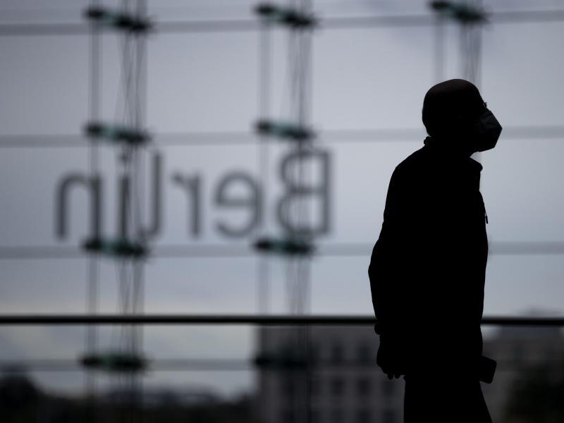 Ein Mann mit Mund-Nasen-Schutz im Berliner Hauptbahnhof vor dem «Berlin»-Schriftzug. Foto: Christoph Soeder/dpa